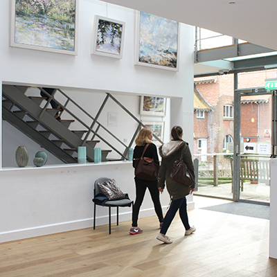 Student walking in the Link Gallery next to paintings