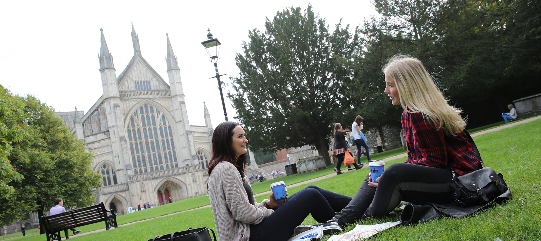 Two girls sat on grass in front of Winchester Cathedral