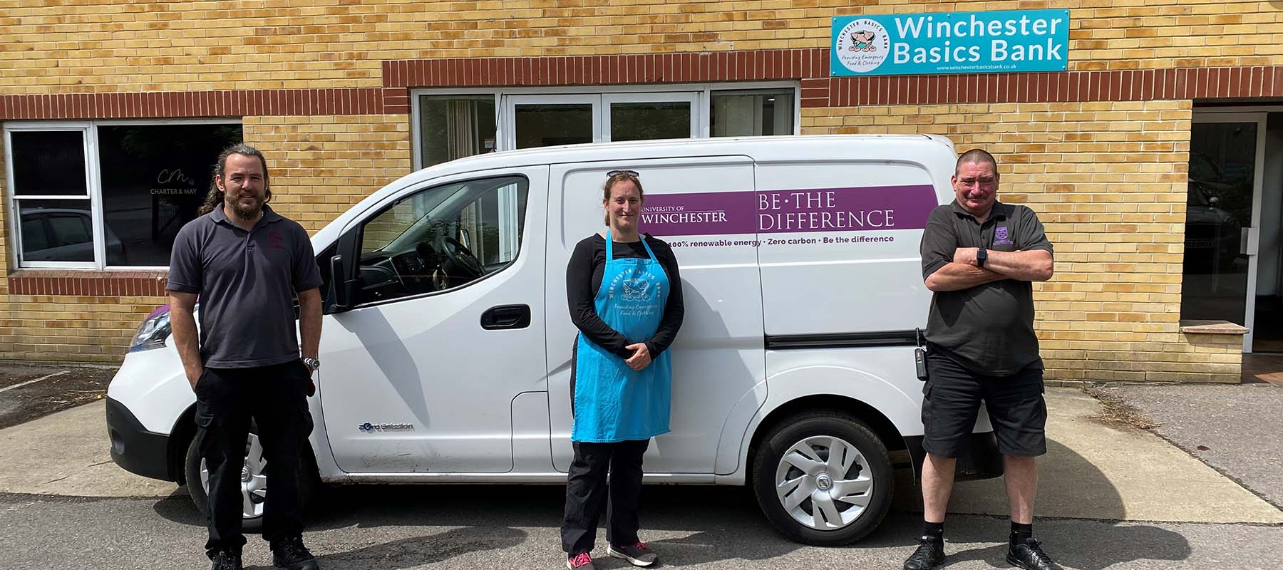 University porters and nightshelter volunteers holding donations by University delivery van