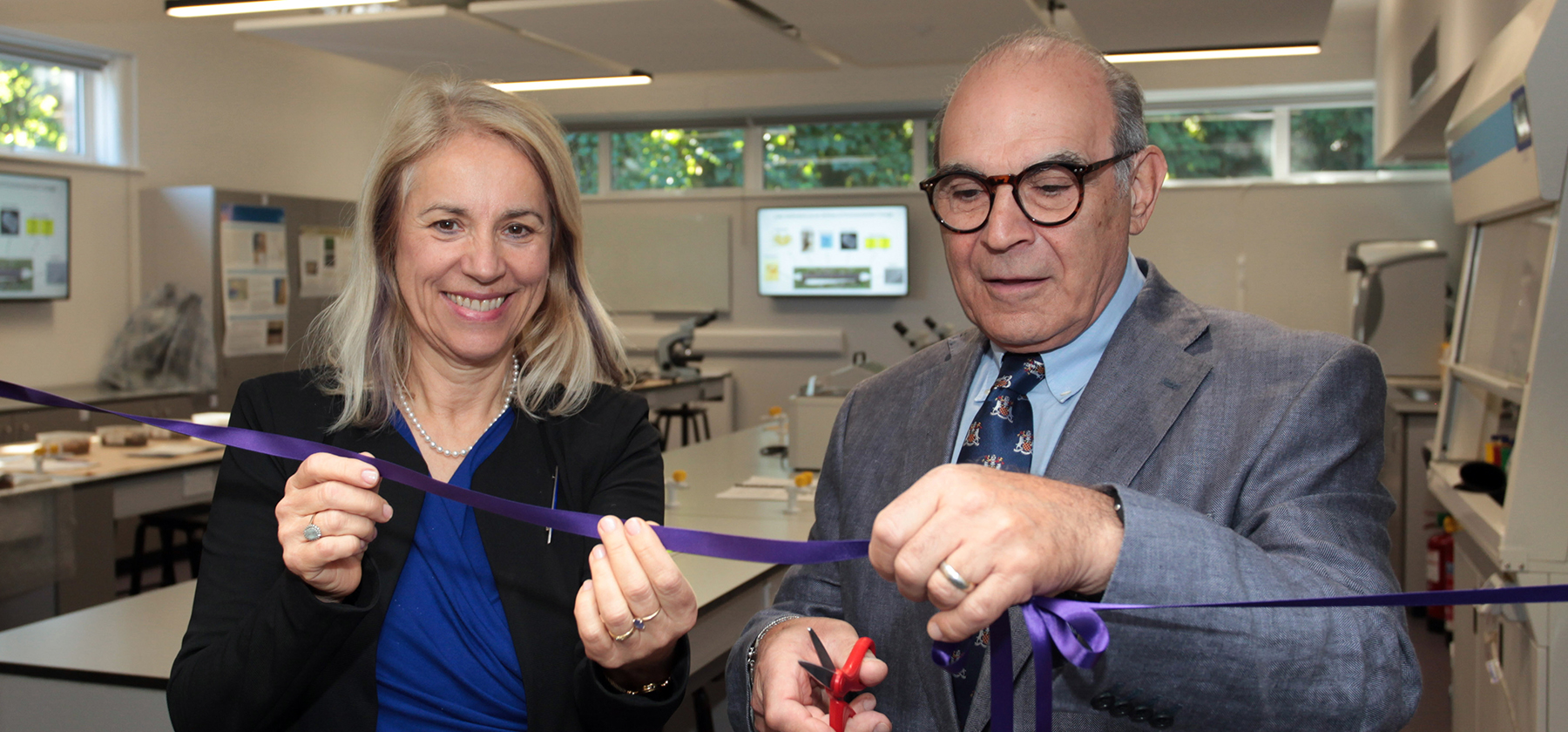 David Suchet cutting a purple ribbon in the forensics lab