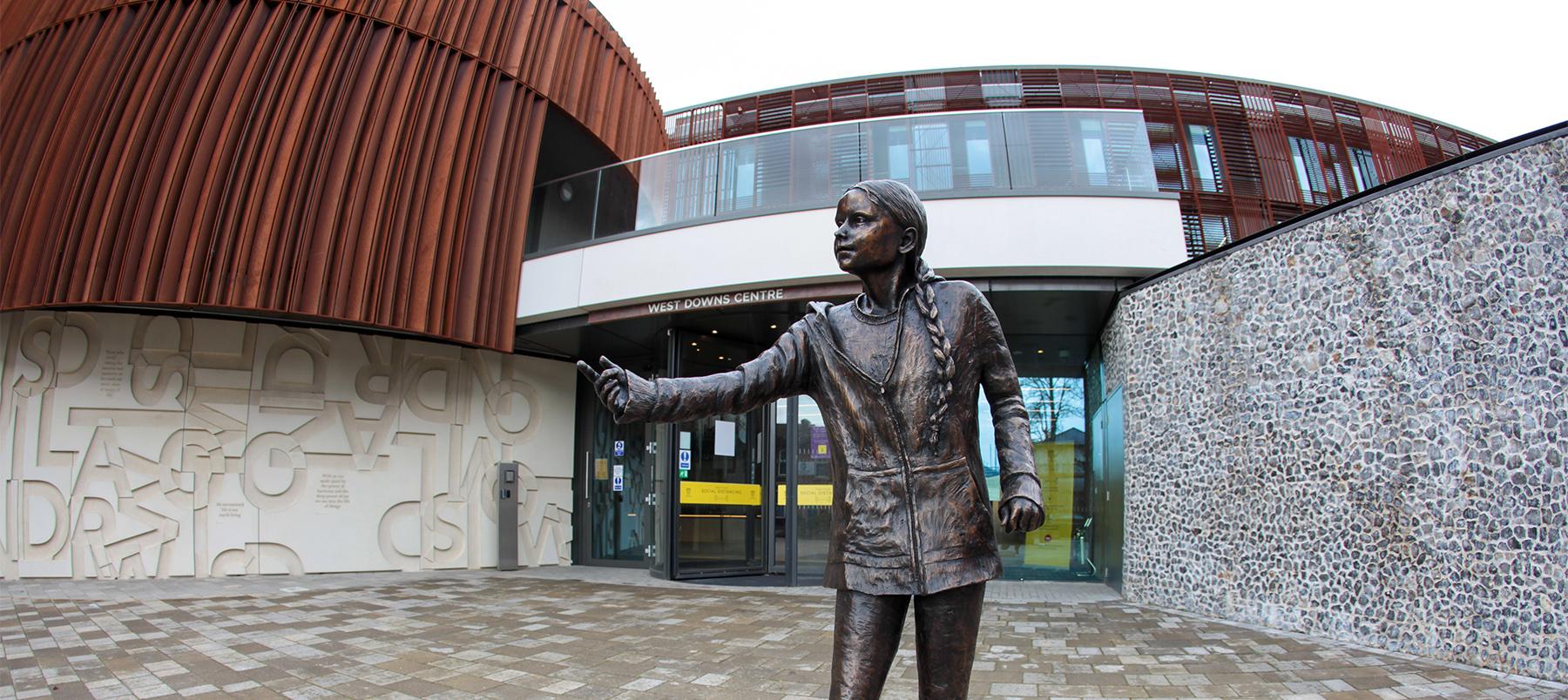 Greta Thunberg bronze statue in front of building
