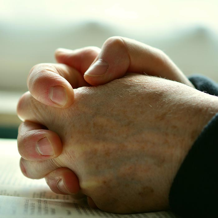 Hands clutched in prayer over an open bible