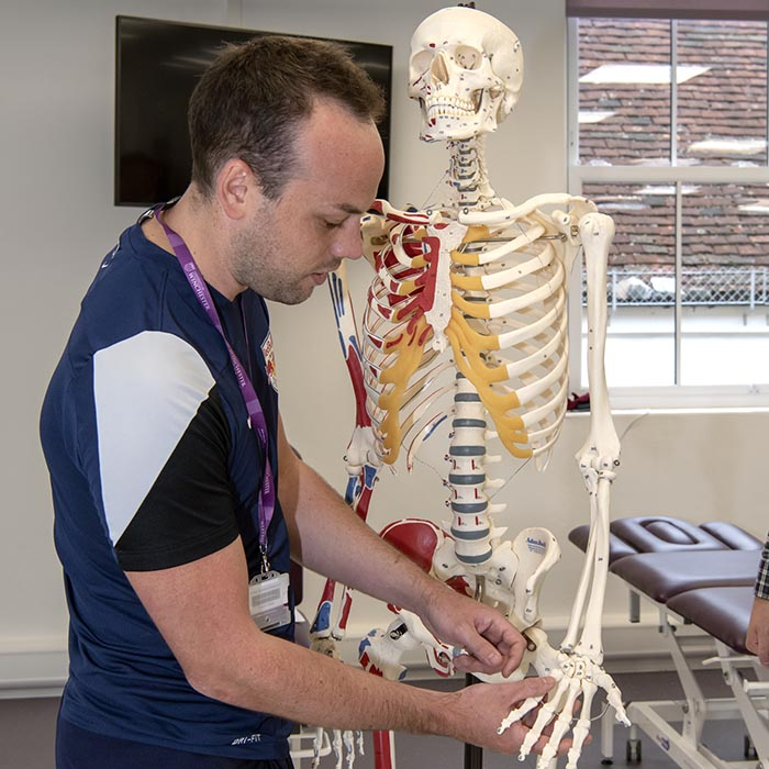 Young man in sports gear standing next to teaching skeleton