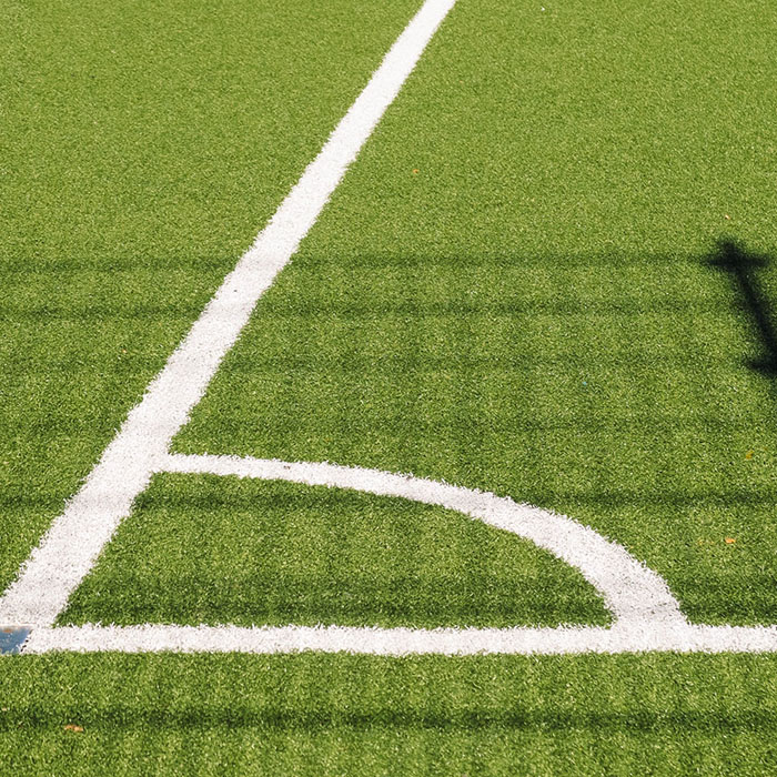 White football pitch corner markings on vivid green grass pitch