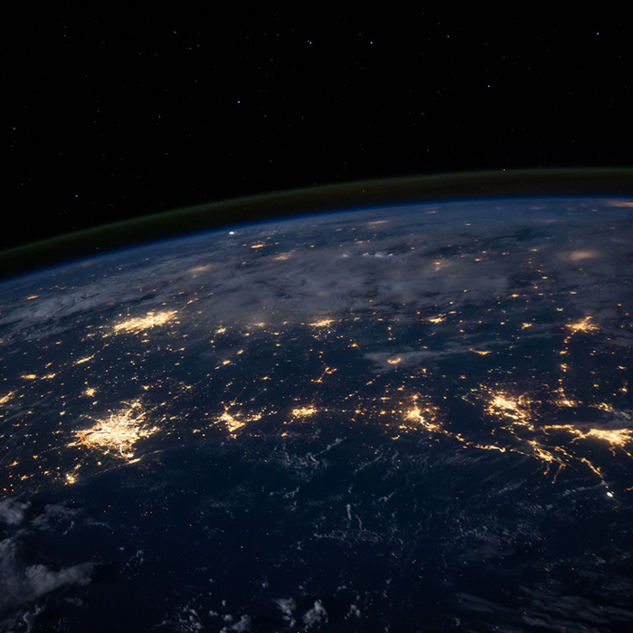 Zoomed out photo of earth in darkness with light from cities