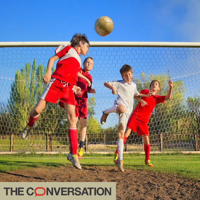 Four young boys playing football, one mid-air after headbutting the ball in front of the goal