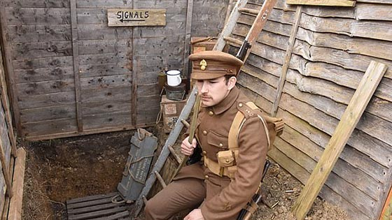 Male student in WWI uniform sitting in trench