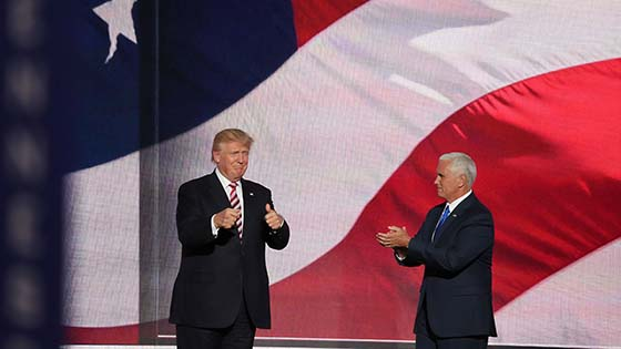 Donald Trump stabnding with another man in front of a US flag backdrop