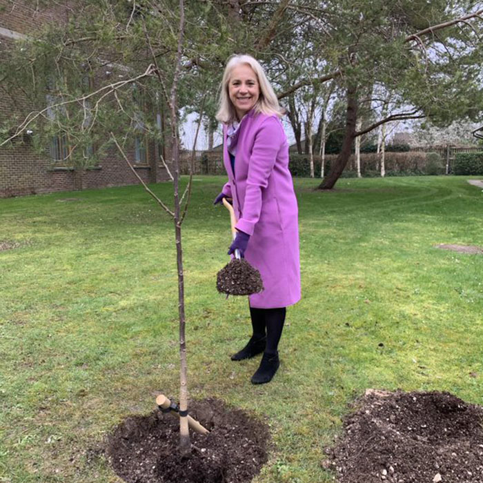 Woman in bright pink coat standing by a tree and holding a spade