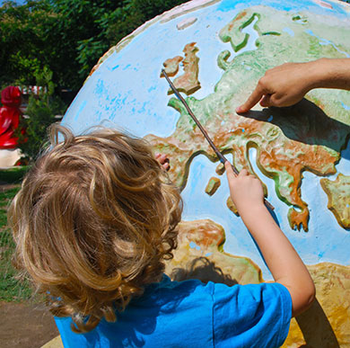 Education expertise at Winchester: child pointing at a place on a miniature planet