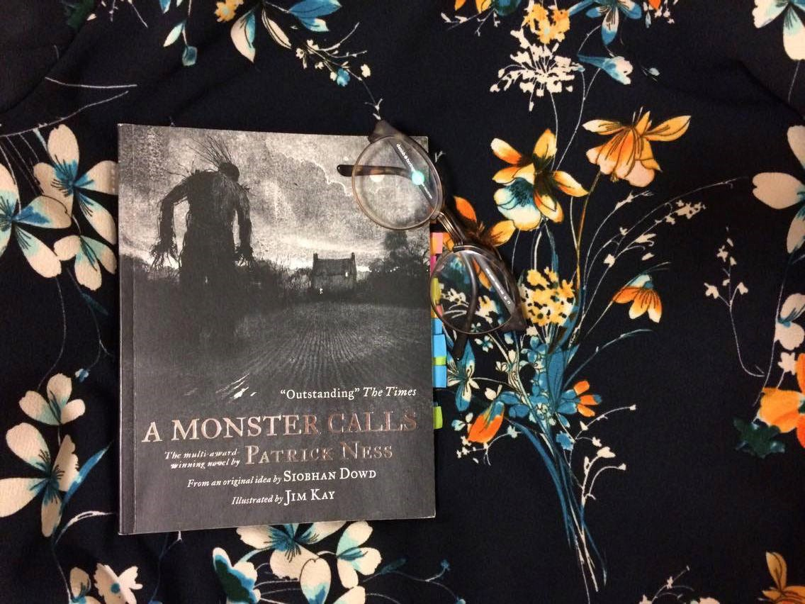 'A Monster Calls' book on a table with glasses on top and a flower background