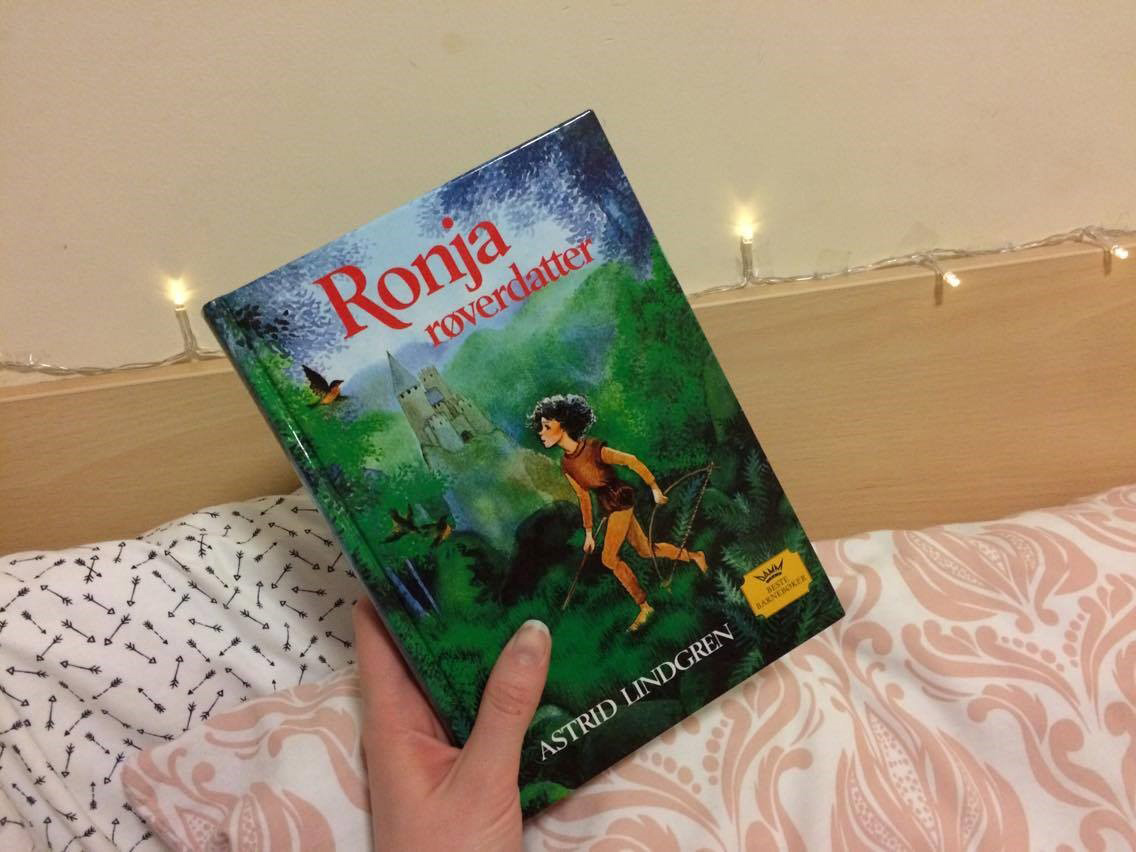 'Ronja roverdatter' book held in front of fairy lights