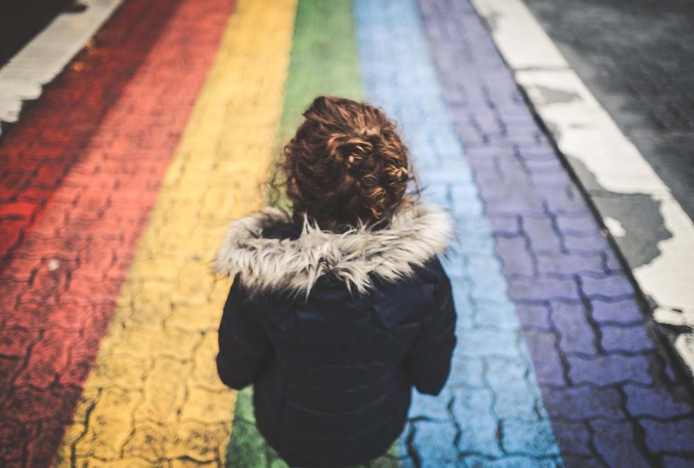 Woman looking at rainbow cobbled street