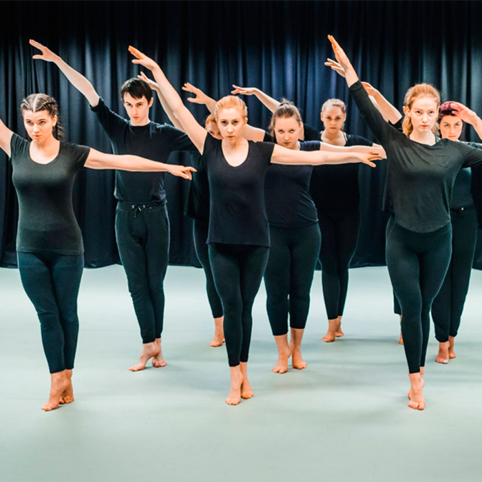 Group of dancers dressed in black standing in a line