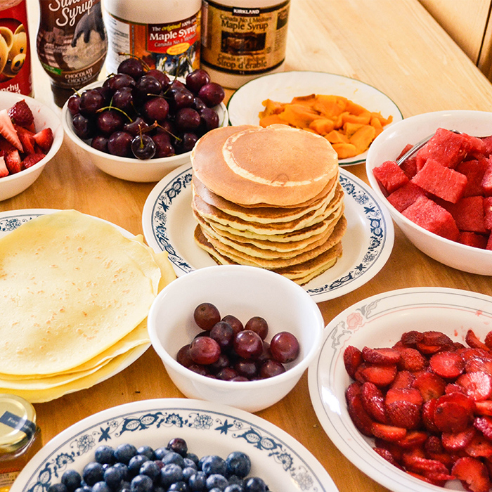 Pancakes and fruit in plates and bowls on a table