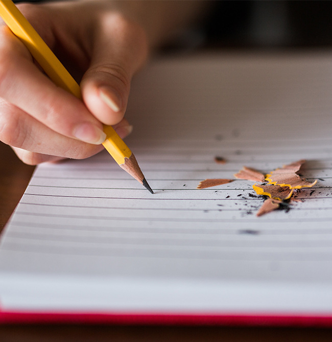 Person writing in a notepad with a pencil, pencil sharpenings on the paper