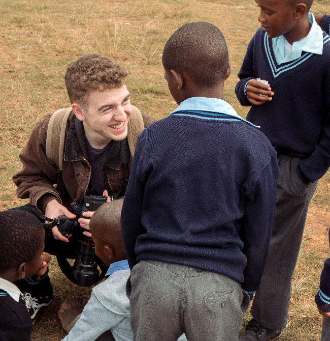 Film production student holding a camera and talking to South African children