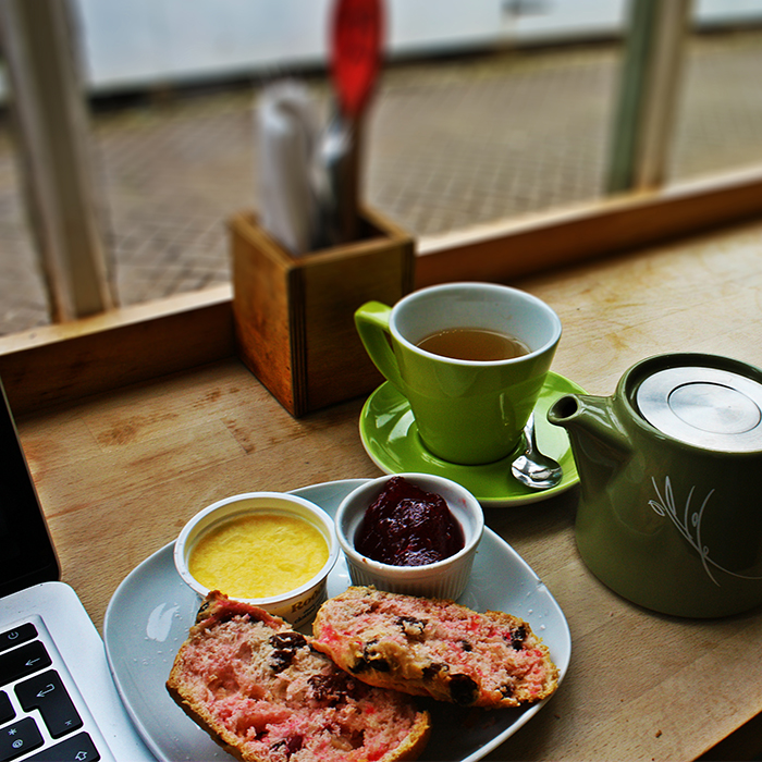 Food and a mug of tea on a table next to a laptop